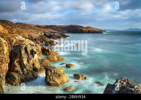 A long exposure of the rocky cliffs at Hushinish on the isle of Harris coast in the Outer Hebrides of Scotland