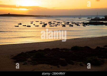 Little fishing boats in the small harbour of Sal Rei at sunset on the island Boa Vista, Cape Verde / Cabo Verde archipelago in the Atlantic Ocean - Stock Photo