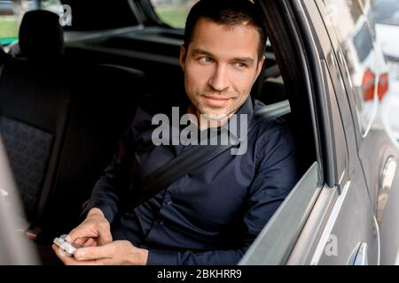 Businessman in a taxi holds a smartphone and looks out the window. Passenger rides in the back seat close-up portrait - Stock Photo