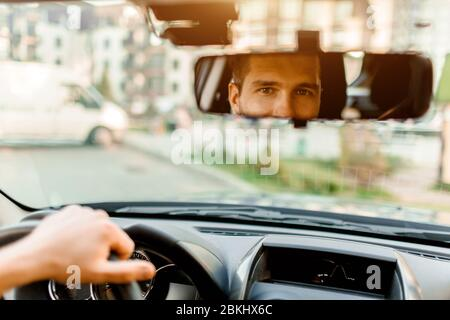 A man looks out the rear view window. In his car. Transportation concept - Stock Photo