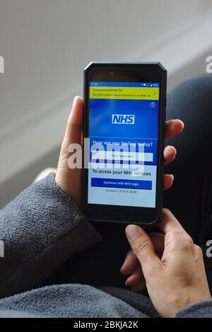 NHS app on smartphone coronavirus COVID-19 link and symptoms check. - Stock Photo