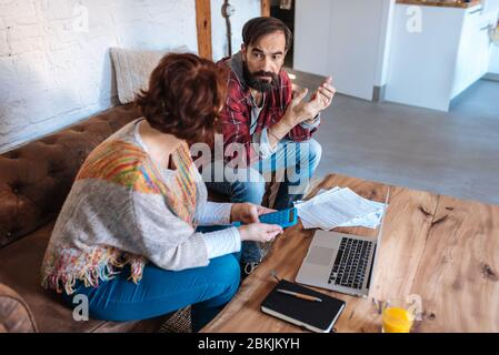 Mature couple sitting at home looking at their finance problems - Stock Photo