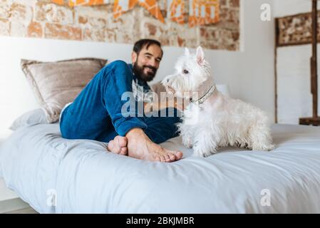 Man relaxed at home sitting in bed with his dog - Stock Photo