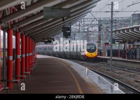 Virgin Trains Alstom class 390 Pendolino train passing Rugby railway station in the rain with the station canopy. - Stock Photo