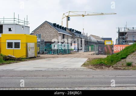 Residential houses being built on a construction site. New neighborhood in Zwolle, the Netherlands. Modern sustainable housing with construction tools - Stock Photo