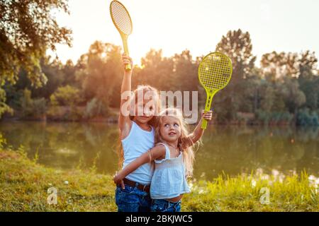 Little girls having fun outdoors after playing badminton. Sisters raise rackets in spring park. Kids activities
