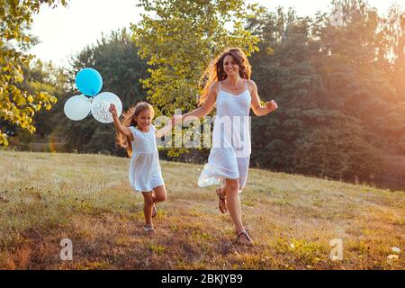 Mother's day. Little girl running with mother and holding baloons in hand. Family having fun in summer park - Stock Photo