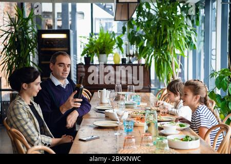 A beautiful family of four having a dinner in a restaurant. The father is pouring wine. - Stock Photo