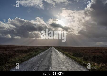 Sun breaking through clouds on an empty straight road. - Stock Photo