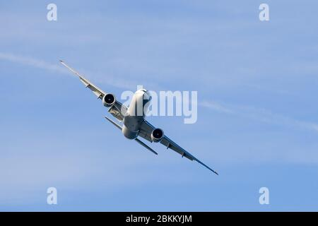 Large commercial airplane making a turn; blue sky background - Stock Photo