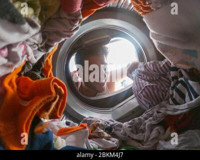 Bearded man using washing machine at home