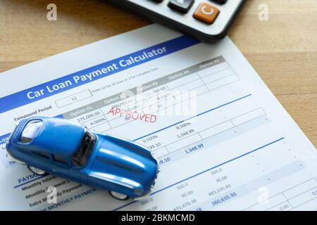 Car loan agreement approved by financial bank.Payment contract  calculator form.A  blue  car with paper  on the table with copy space. - Stock Photo