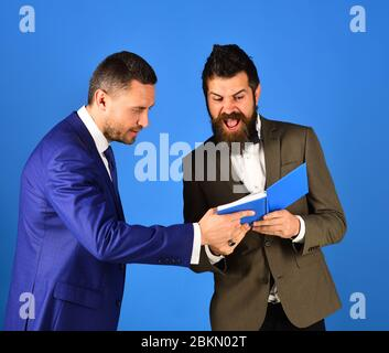 Machos in classic suits argue about schedule. Men with mad faces read blue book. Business knowledge and management concept. Businessmen with beards discuss business looking into notes. - Stock Photo