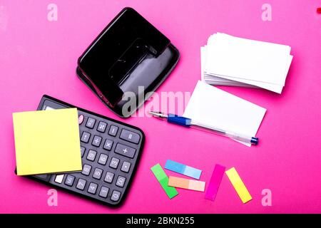 Business and work concept. Hole punch, pen, notes, colorful bookmarks and other office tools. Business cards with blank space and calculator. Stationery on pink background, top view.