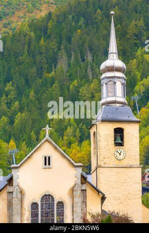Chamonix Mont Blanc, France, street view with bell tower of catholic church of St Michel in autumn, flowers and houses in town