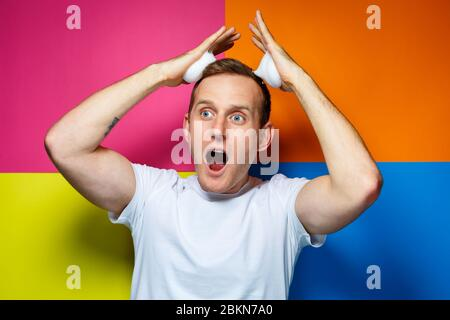 portrait of a young cheerful guy on a multi-colored background, dressed in a white T-shirt, poured hair foam in his hands, creates a fashionable hairs - Stock Photo