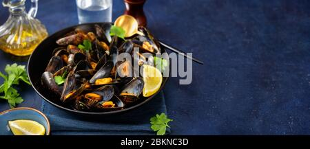 Cooked mussels in a plate with parsley and lemon on a trendy blue background