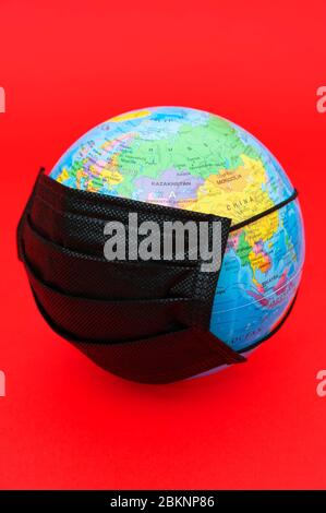 Terrestrial globe model with black surgical mask isolated on red background. Concept: Quarantined earth. Protection against Coronavirus (COVID-19). - Stock Photo