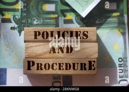 Policies and procedures words written on wooden blocks laying on some banknotes of 100 Euro value. Law legal financial regulation concept