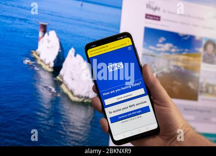 Dorset, UK. Tuesday 5 May 2020. NHS contact tracing app is launched on the Isle of Wight in the UK. Smartphone shown with the NHS app and landmark The Needles behind. Credit: Thomas Faull/Alamy Live News - Stock Photo
