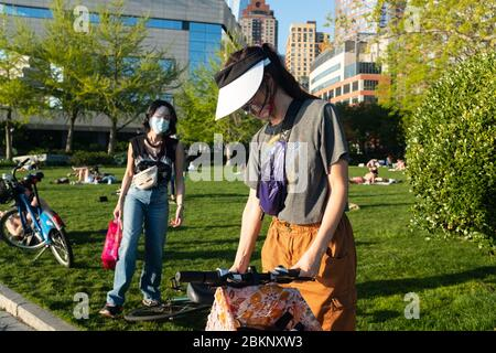 Women wearing protective face masks enjoying the warm weather in Battery Park City during the COVID-19 coronavirus pandemic. - Stock Photo