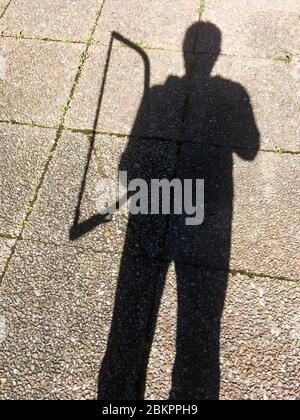 Shadow of a man holding a saw, Bron, France - Stock Photo