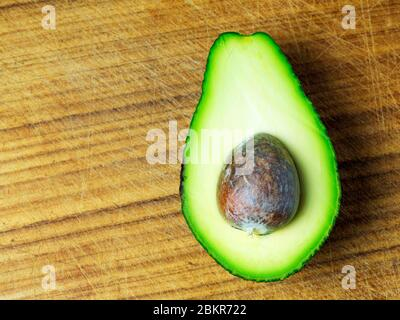 Half an avocado with the stone left in on a wooden chopping board - Stock Photo