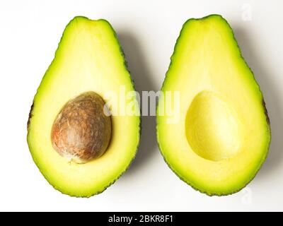 Two avocado halves the same way up with the stone left in one half on a white background - Stock Photo