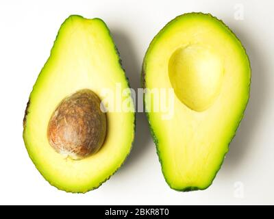 Two avocado halves opposite ways up with the stone left in one half on a white background - Stock Photo