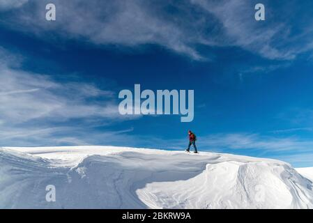 France, Drome, Vercors, Hauts-Plateaux, top of the Montagnette (1972m), hiker walking towards the summit on snow worked by the wind - Stock Photo