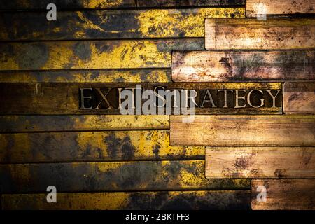 Photo of real authentic typeset letters forming Exit Strategy text on vintage textured grunge copper background