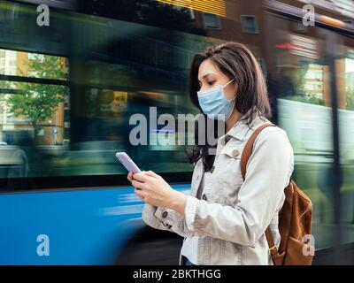 Woman standing in the bus stop. She is wearing a protective mask for the prevention of a virus. Coronavirus concept.