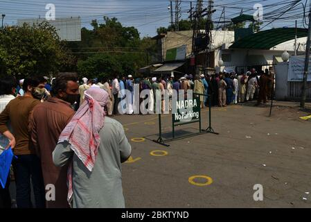 A large numbers of people stand in queue without maintaining social distancing at NADRA office in Shimla Hill area as to get their national identity cards. NADRA reopened its offices across the country to facilitate the general public in Lahore. Residents wearing facemasks line up in a queue outside the National Database and Registration Authority (NADRA) office for new registrations and biometric verification under the governmental Ehsaas Emergency Cash Programme for families in need during a government-imposed nationwide lockdown as a preventive measure against the COVID-19. (Photo by Rana S - Stock Photo