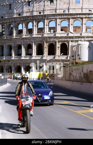 Man wearing a medical face mask, on motorbike passes in front of the Colosseum during the lockdown for ilo Coronavirus Covid 19. Rome, Italy, Europe, EU. - Stock Photo