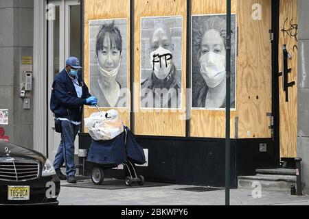 """New York City, USA. 05th May, 2020. A postal worker wearing a mask walks past a boarded store with posters of other 'frontline"""" workers in the Soho neighborhood of New York City, NY, May 5, 2020. The usually bustling and vibrant neighborhood lined with high-end name brand boutiques is seen almost deserted as stores remain closed or are vacant due to the economic impact of the COVID-19 pandemic. (Anthony Behar/Sipa USA) Credit: Sipa USA/Alamy Live News - Stock Photo"""