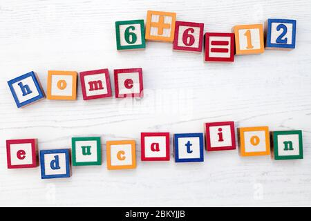 A set of children's wooden spelling blocks spell out the words home education and a simple sum. - Stock Photo