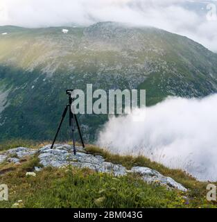 The mountain passes and the Alps are a paradise for photographers. Tripod. View of the clouds and the first rays of sun from the road of Grimsel Pass - Stock Photo