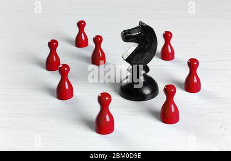 Big black knight chess piece surrounded by smaller red pawns on a white wooden table - Stock Photo