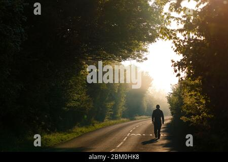 A man walks along a country lane on a misty morning at Fairburn Ings Nature Reserve.