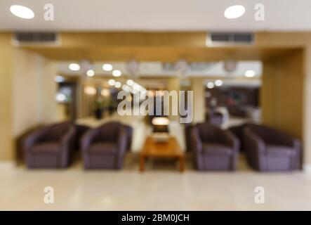 Blurred waiting area in hotel with brown armchairs - Stock Photo