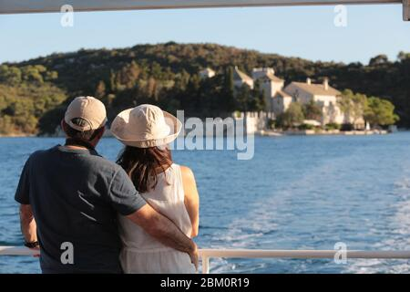 A cuddled couple on a ship looking into the sea landscape