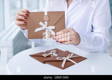 close-up photo of gift certificate, card, wedding invitation card. female hands holding a bronze invitation envelope with a wax seal