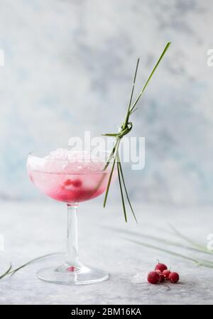 Pink mocktail close up. Beverage with rose and prosecco wine in drinkware. Exotic French Martini cocktail portion with crushed ice in glassware - Stock Photo
