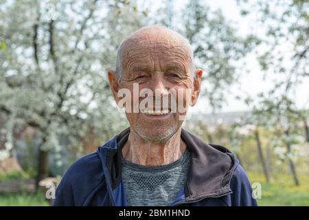 Close up portrait of a happy old man pensioner in sportswear who smiling and looking at the camera - Stock Photo
