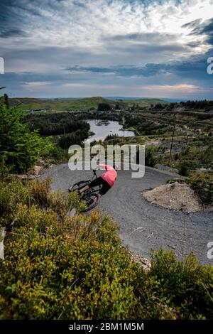 A man rides a mountain bike on a trail at Nant-yr-Arian in Wales. - Stock Photo