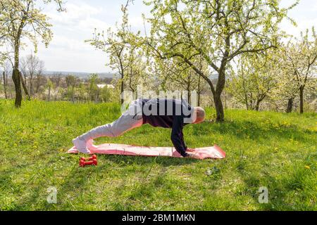 Old aged man doing plank on the yoga mat in the park