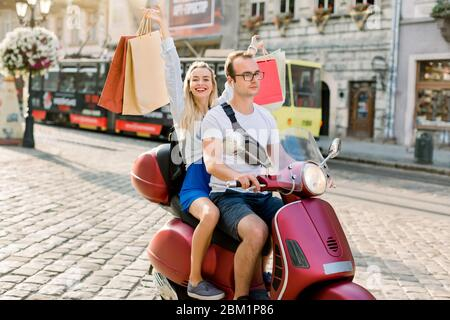 Happy young couple riding a scooter in the city on a sunny day. Handsome man in glasses rides a moped, while his charming blond girlfriend behind - Stock Photo