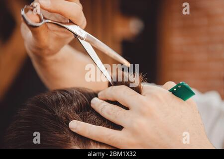 Close-up of man haircut, master does the hair styling in barber shop - Stock Photo