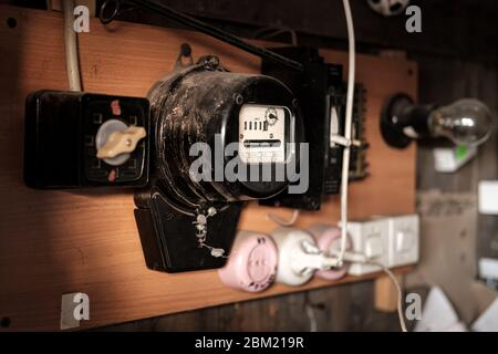 Old electric meter for calculating energy consumption is hanging in the barn, next to sockets and a light bulb. Russia. - Stock Photo