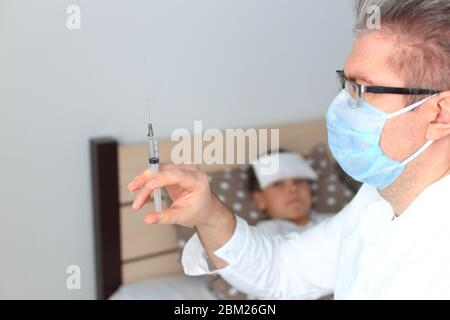 The doctor is going to give an injection to a sick child - Stock Photo